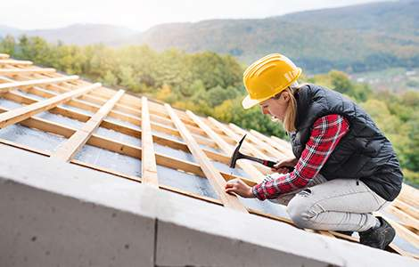 artisan couvreur construisant une toiture neuve