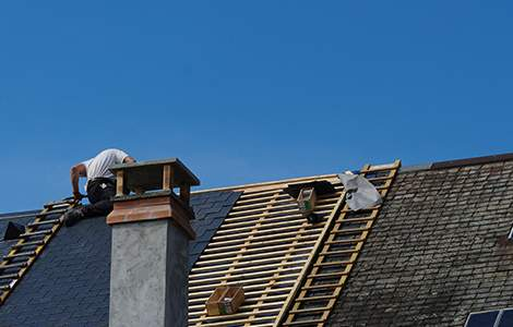 artian couvreur rénovant une toiture