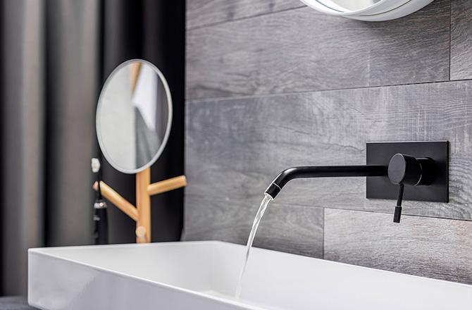 Une vasque blanche design et sa robinetterie noire
